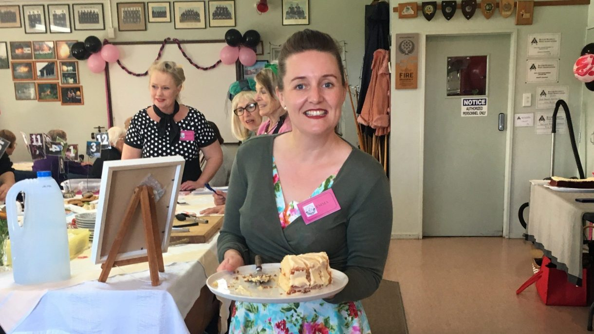 Emma Sherie serving cake at CommuniTea
